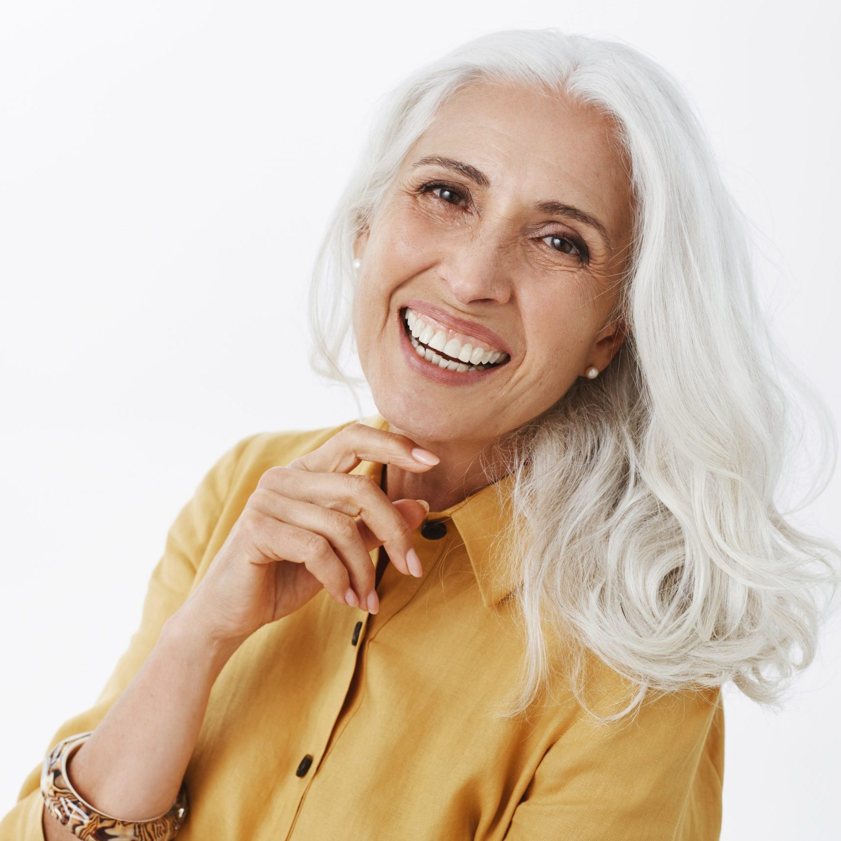 Close-up shot of happy delighted and accomplished charming european elderly female with white hair in yellow trench coat touching face gently laughing from joy feeling pretty and energized. Copy space