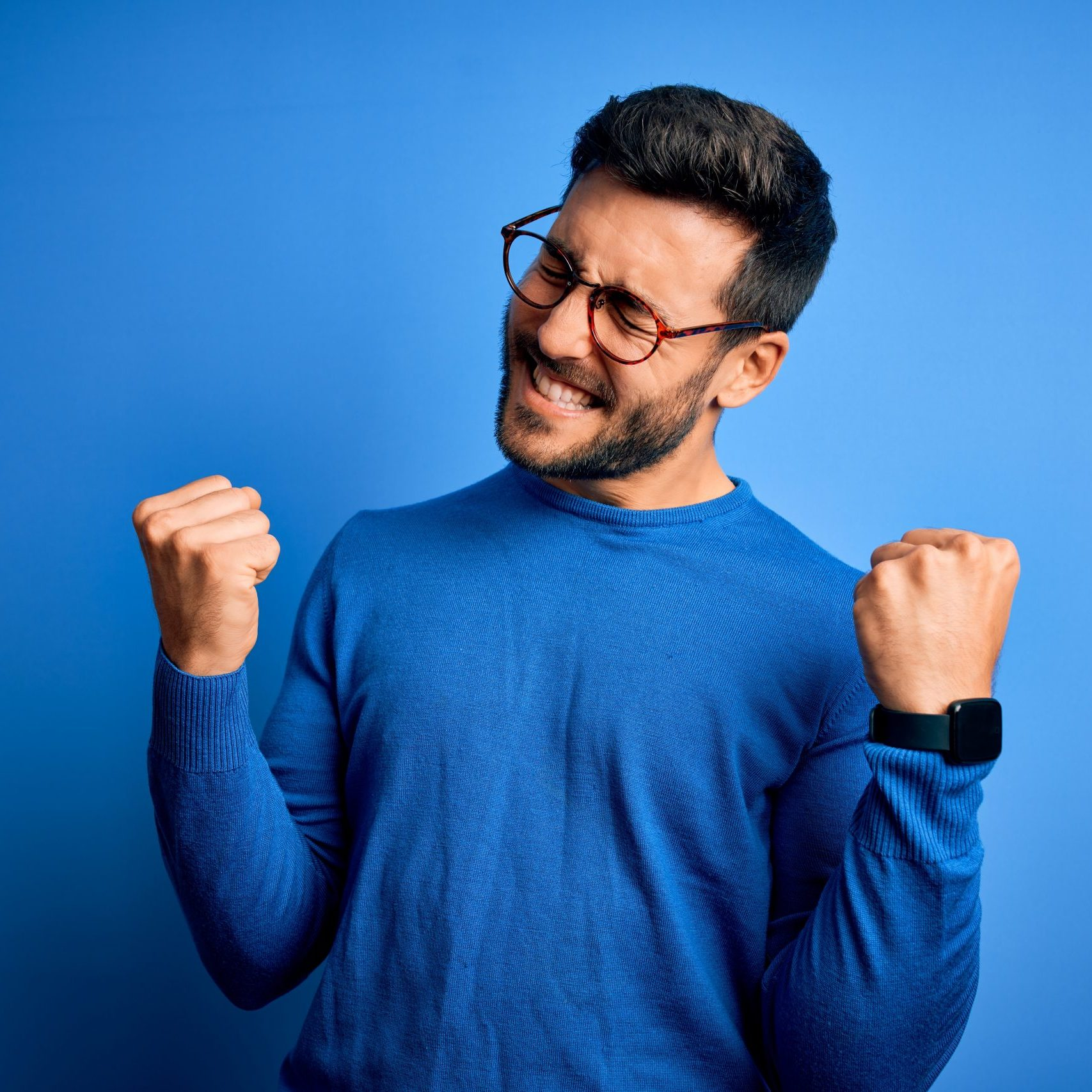 Young handsome man with beard wearing casual sweater and glasses over blue background very happy and excited doing winner gesture with arms raised, smiling and screaming for success. Celebration concept.
